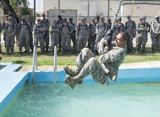 Chaplain candidates watch basic military trainees attempt to complete one of the Creating Leader Airmen Warriors, or CLAW, course's obstacles during a tour of the Basic Expeditionary Airmen Skills Training at Joint Base San Antonio-Lackland, Texas, July 5, 2017. The tour was part of the Chaplain Candidate Intensive Internship. (U.S. Air Force photo by Senior Airman Krystal Wright)