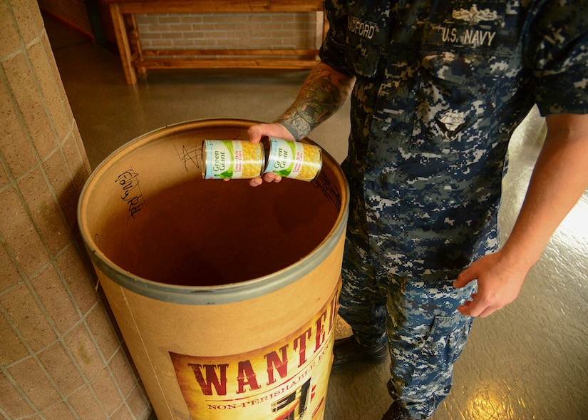 Charleston, S.C. (Jul 17, 2017) Petty Officer 2nd Class Christopher Bradford, Naval Support Activity administrative assistant, donates canned food in support of Feds Feed Families at the All Saints Chapel on Joint Base Charleston - Weapons Station. Feds Feed Families was created to help food banks and pantries stay stocked during summer months when they traditionally see a decrease in donations and an increase in need.
