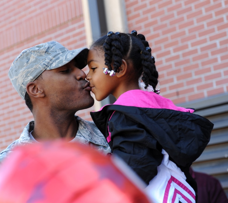 Then Tech. Sgt. Alvin Dyer, the 23rd Civil Engineering Squadron (CES) heating, ventilation and air conditioning NCO in-charge, gives his daughter, Cassidy, a kiss after he was promoted to master sergeant under the Stripes for Exceptional Performers program Dec. 29, 2009. Now a chief master sergeant, Dyer is the superintendent of the 354th CES. (U.S. Air Force photo by Airman 1st Class Benjamin Wiseman)