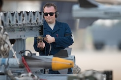 U.S. Air Force Staff Sgt. Jonathan Deacon, 1st Aircraft Maintenance Squadron weapons team chief, secures a weapons load trailer while loading training munitions on to an F-22 Raptor at Joint-Base Langley-Eustis, Va., July 11, 2017. The 1st Fighter Wing conducted night flying operations to give pilots an opportunity to maintain currencies on skills required to fly in the dark.  (U.S. Air Force Photo/Master Sgt. Benjamin Wilson)
