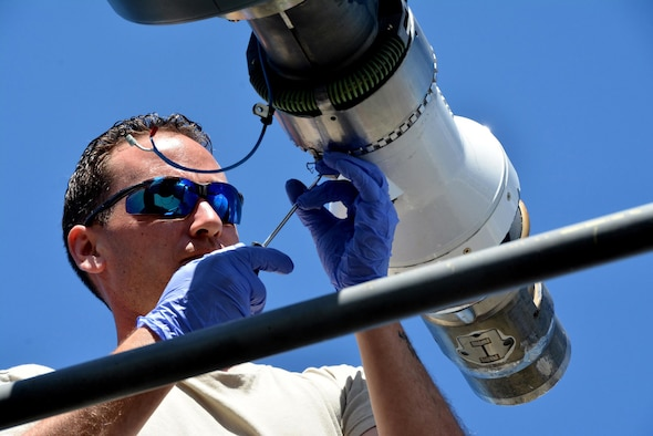Senior Airman Travis Krause, a crew chief assigned to the 507th Air Refueling Wing, Tinker Air Force Base, Oklahoma, removes the boom nozzle from a KC-135R Stratotanker in order to connect a drogue adapter and drogue. (Master Sgt. Grady Epperly)