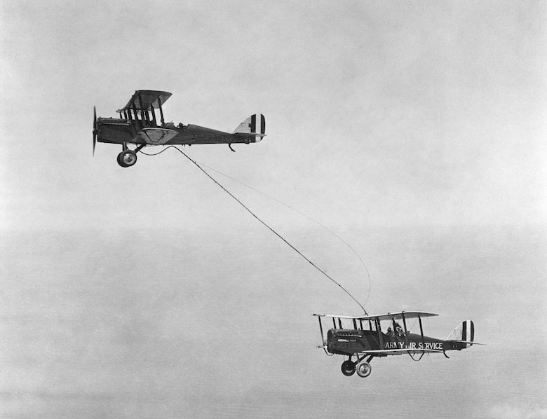 A plane flown by Capt. Lowell H. Smith and Lt. John P. Richter receives fuel from a plane flown by 1st Lt. Virgil Hine and 1st Lt. Frank W. Seifert during one of the first recorded aerial refuelings. ARSAG has been working to improve aerial refueling for nearly 40 years.