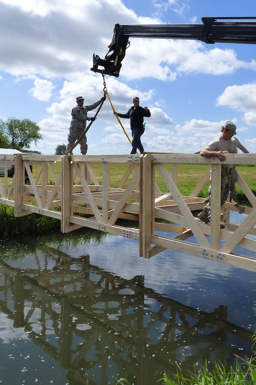Simmons and the Soldiers use a crane to put the bridge in place.