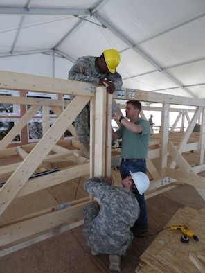 Air Force Reserve Maj. David Simmons Jr. works on construction of the bridge with Soldiers from the Army Europe 21st Theater Sustainment Command's 15th Engineer Batallion.