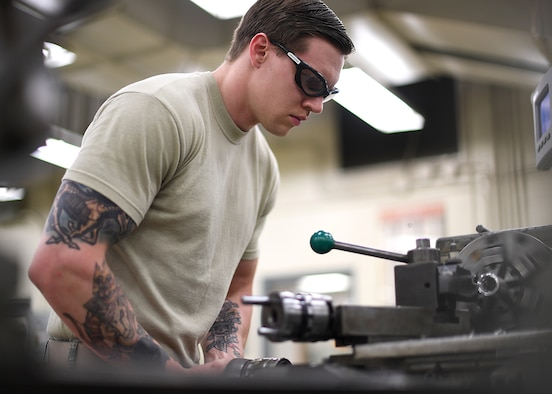 Airman 1st Class Charles Buchanan, 69th Maintenance Squadron aircraft metals technology journeyman, uses a lathe to build a new part July 13, 2017, on Grand Forks Air Force Base, N.D. Buchanan and other Airmen with the 69 MXS fabricated a new part for an RQ-4 Global Hawk, which allowed the Air Force to save money and the mission to continue. (U.S. Air Force photo by Senior Airman Ryan Sparks)