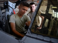 Airmen Corbin Broglio and Tryston Stanfield, 362nd Training Squadron A-10 crew chief apprentice course students, work on raising the windshield to allow access to the avionics boxes. Avionics boxes would need to be accessible during and electronic malfunction. (U.S. Air Force phot by Senior Airman Robert L. McIlrath)