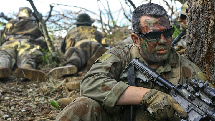 A soldier with face paint guards an observation post next to a tree.
