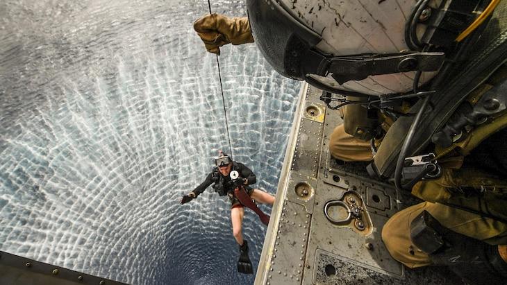 A sailor hoists another sailor into a helicopter over water.