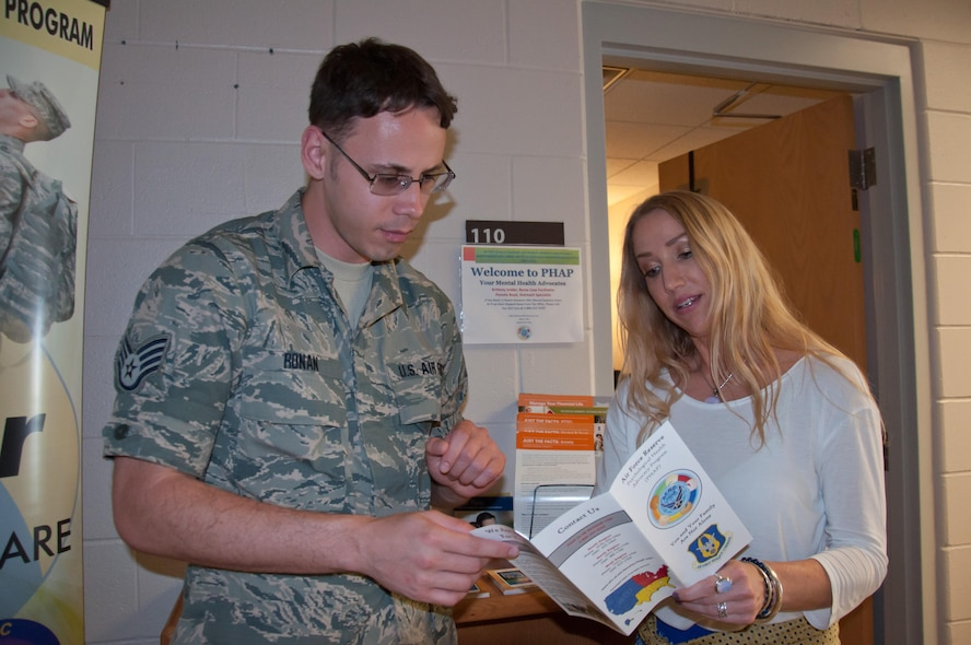 Pamela Boyd, Psychological Health Advocacy Program Outreach Specialist, provides program literature to Staff Sgt. Samuel Ronan, 445th Customer Support NCOIC, to support the 3,000 members of the reserve squadron June 15, 2017. PHAP assists members and families as they deal with life's stressors. (U.S. Air Force photo/John Harrington)