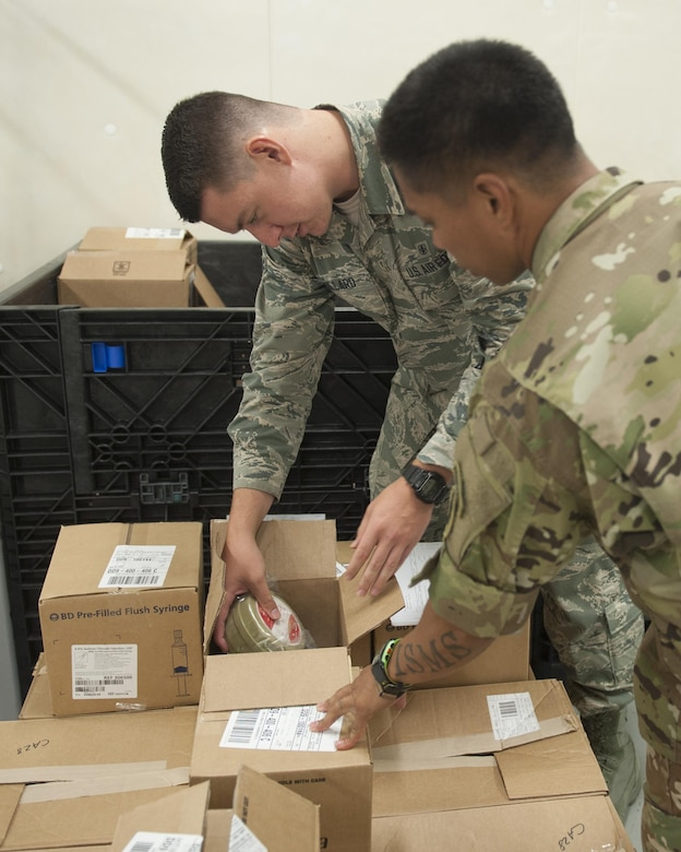 U.S. Air Force Airman 1st Class Rock Remillard, 18th Medical Support Squadron medical logistics technician, and U.S. Army Staff Sgt. Don Kosht, 1-1 Special Forces Group medical logistics NCO, inspect materials during a Theater Lead Agent for Medical Materiel – Pacific (TLAMM-P) joint exercise July 13, 2017, at Kadena Air Base, Japan. TLAMM-P is crucial to humanitarian efforts in getting needed medical supplies to units in the field. (U.S. Air Force photo/ Airman 1st Class Greg Erwin)