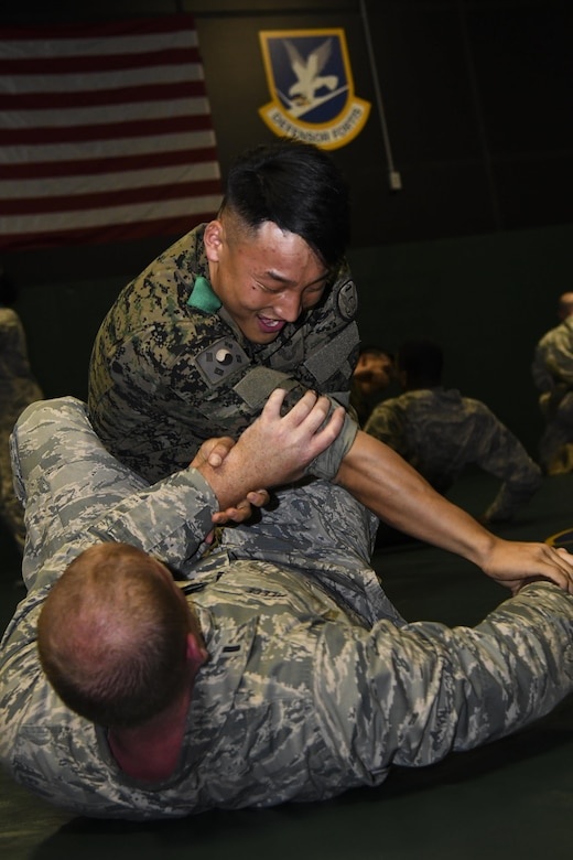 U.S. Air Force 1st Lt. Brett Meece, 51st Security Forces Squadron member, participates in hand to hand combat training with a ROK counterpart during joint combat training at Osan Air Base, Republic of Korea, July 19, 2017. This is the first time this type of joint training has been practiced and was integrated into the Combat Readiness Course, an intensive 10-day course that is held monthly by the 51st SFS. (U.S. Air force photo by Airman 1st Class Gwendalyn Smith)