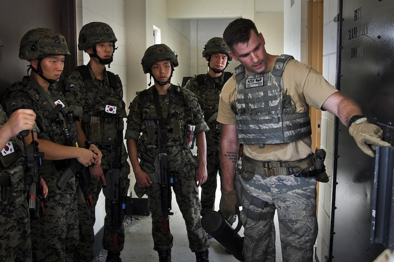 U.S. Air Force Staff Sgt. Cliff Coppenbarger teaches a group of ROK Special Forces members building clearing procedures during joint combat training at Osan Air Base, Republic of Korea, July 19, 2017. The sessions included different types of combat techniques that might need to be employed during combat situations, including hand to hand combat and combat shoot communication. (U.S. Air force photo by Airman 1st Class Gwendalyn Smith)