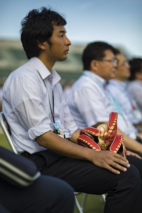 A Japanese local holds his baseball gloves as he watches the scoreboard lighting ceremony at Kizuna Stadium in Iwakuni City, Japan, July 19, 2017. Upon completion of the stadium, access will be granted to the people of Iwakuni city and the surrounding towns in the prefecture, to include the service members and their families. (U.S. Marine Corps photo by Cpl. Joseph Abrego)