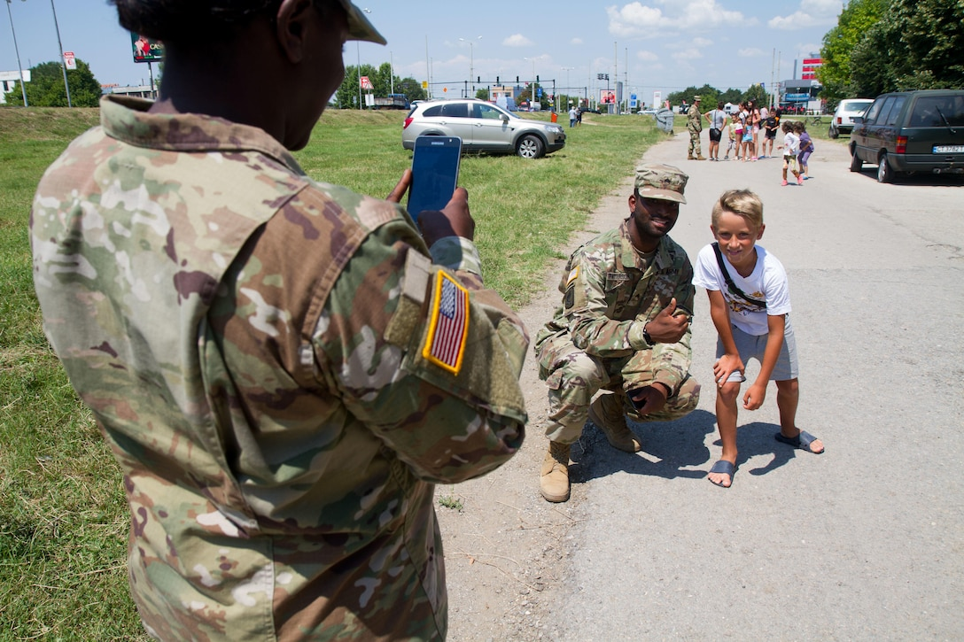 Sgt. Donald Patterson, civil affairs soldier with 361st Civil Affairs Brigade, poses for a photo with a local of Ruse, Bulgaria at a static display of 2nd Cavalry Regiment strykers and Bulgarian military vehicles, July 17 (U.S. Army Reserve photo by Capt. Jeku Arce, 221st Public Affairs Detachment).