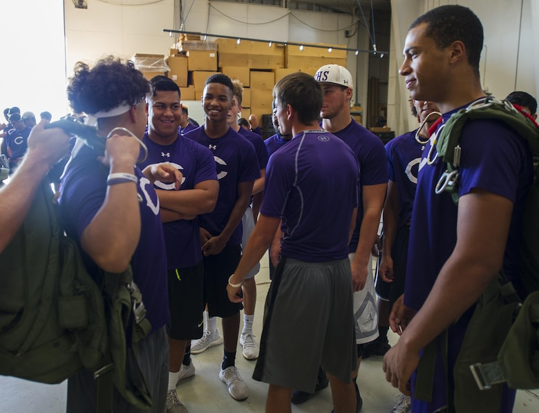 Clovis High School football players try on parachutes at the 26th Special Tactics Squadron during their tour at Cannon Air Force Base, NM, July 19, 2017. Students experienced what it felt like to wear gear that 26th STS Airmen are expected to complete the mission with. (U.S. Air Force photo by Senior Airman Lane T. Plummer)