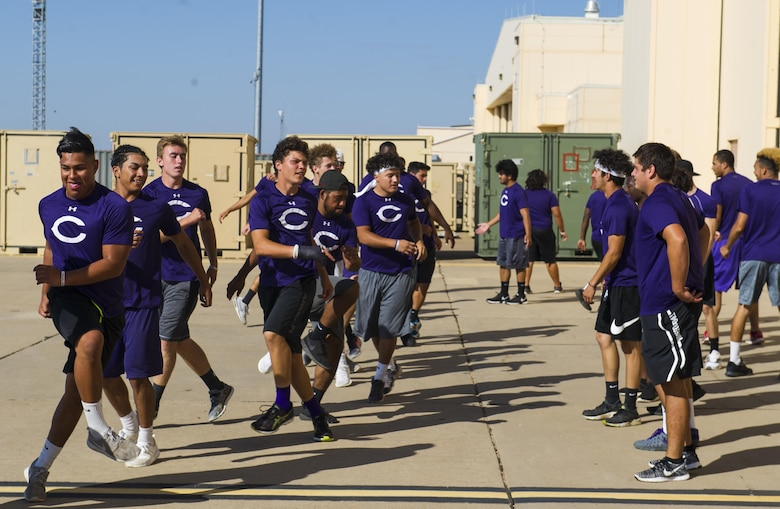 Clovis High School football players exercise on the flightline during their tour at Cannon Air Force Base, NM, July 19, 2017. From practicing physical form on the flightline to sweating through sets in the gym, the students followed a regimen that special tactics Airmen use to maintain a high standard of physical ability. (U.S. Air Force photo by Senior Airman Lane T. Plummer)