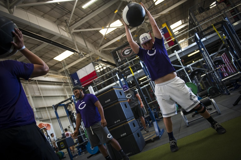 "Clovis High School football players exercise at the 26th Special Tactics Squadron's gymnasium during their tour at Cannon Air Force Base, NM, July 19, 2017. Students followed a regimen constructed and used by 26th STS Airmen in what one of them describes as a ""world class facility."" (U.S. Air Force photo by Senior Airman Lane T. Plummer)"