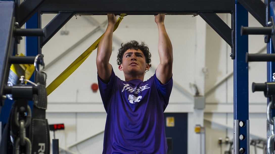 A Clovis High School football player exercises at the 26th Special Tactics Squadron's gymnasium during his team's tour at Cannon Air Force Base, NM, July 19, 2017. The students, currently in their pre-season form, endured the rigorous regimen that 26th STS Airmen follow to maintain mission readiness. (U.S. Air Force photo by Senior Airman Lane T. Plummer)