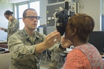 Air Force Capt. Matthew Stoltz, a physician assistant with 171st Air Refueling Squadron, examines the eyes of Kim Harrell-Jones, a patient attending Innovative Readiness Training Louisiana Care 2017, at Amite High School in Amite, La., July 15, 2017. IRT Louisiana Care 2017 offers optometry, dental and medical care to the local community at no cost to patients. (U.S. Marine Corps Photo by Lance Cpl. Niles Lee/Released)