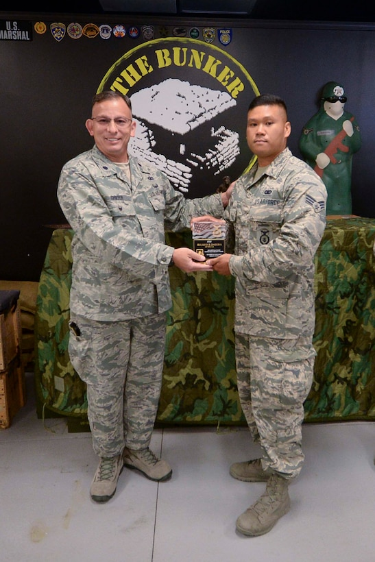 Lt. Col. Brian Griefer, Operations and Training Branch Chief, NCB/A4S present the Air National Guard Security Forces 2016 Unit of the Year award to Senior Airman Jason Daquinas, 129th Security Forces, during an awards ceremony at Moffett Air National Guard Base, Calif., July 18, 2017. (U.S.Air National Guard photo by Senior Airman Zachiah Roberson/released)
