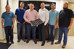 Dung Su, Frank Neukam, Sam Pratt, Jonathan Hopkins, Keith Brennan and Ryan Franke, all employees with Naval Surface Warfare Center, Carderock Division, display additively manufactured aviation parts they rapidly produced in a first-of-its-kind response to a critical need to restore stalled training operations for the T-45 Goshawk. Photo by Dustin Diaz