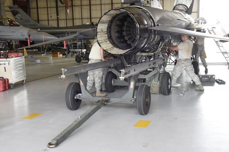 114th Aircraft Maintenance Squadron engine shop Airmen remove the engine of an F-16 during the De-paneling Phase of a phase maintenance inspection at Joe Foss Field, July 8, 2017.  Each aircraft is required to go through a phase inspection every 400 flight hours to ensure all systems are functioning within Air Force regulations.  (U.S. Air National Guard photo by Master Sgt. Christopher Stewart/Released)