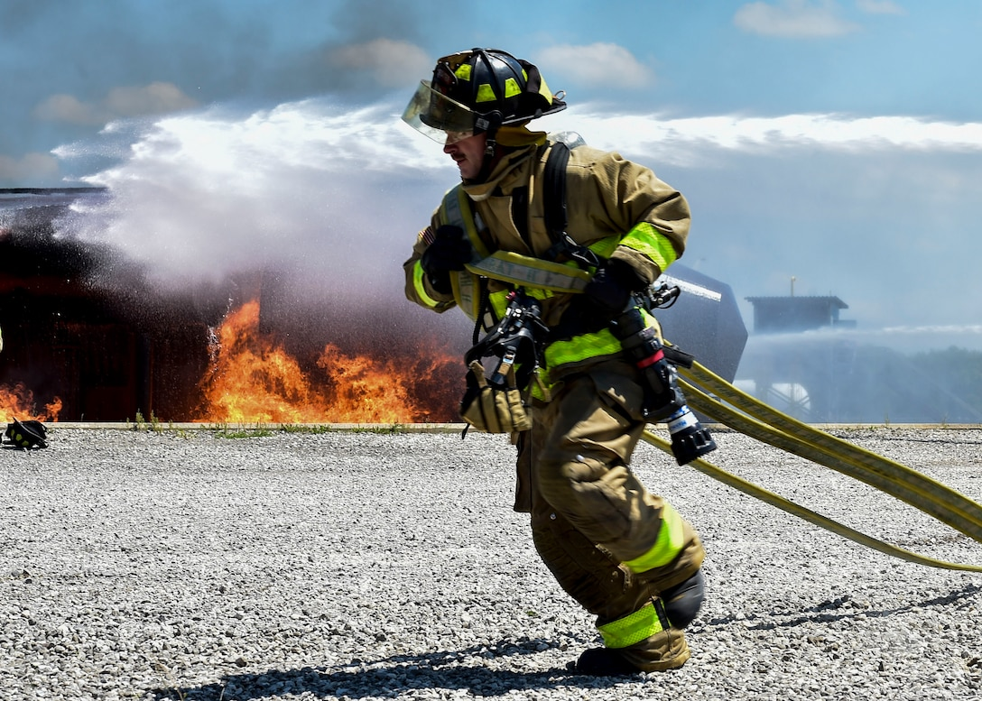 An Army firefighter of the 5694th Engineer Detachment from the Army National Guard stationed in Mansfield, Ohio, rushes to unravel a fire hose so he may combat a blaze during an airport rescue firefighting exercise July 18, 2017,  here. The YARS burn pit provides real time firefighting training experiences for not only YARS but for its neighbors too. (U.S. Air Force Photo/Senior Airman Jeffrey Grossi)