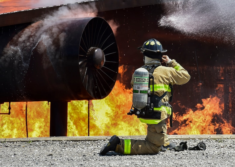 An Army firefighter of the 5694th Engineer Detachment from the Army National Guard stationed in Mansfield, Ohio, straps on his fire helmet after donning his gas mask during an airport rescue firefighting exercise July 18, 2017, here. The 5694th is at YARS for one week while completing their annual training. (U.S. Air Force Photo/Senior Airman Jeffrey Grossi)