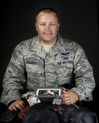 Tech. Sgt. Ryan Padgett, 570 Global Mobility Squadron unit training manager, displays the keepsakes that travel along with him on his worldwide missions, July 18, 2017. Men and women serving their country in all branches of the military have traditionally kept meaningful mementos or talismans close to them for good luck, as reminders, to bring comfort or other deeply felt personal reasons. Digitaly altered for security reasons. SSN blurred in camera RAW. (U.S. Air Force photo Illustration/Heide Couch)
