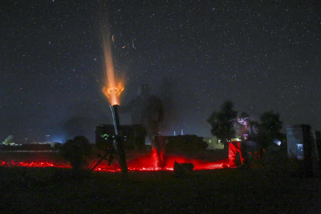 Marines fire a nonexplosive illumination round at night from an 81 mm mortar to deter enemy activity.