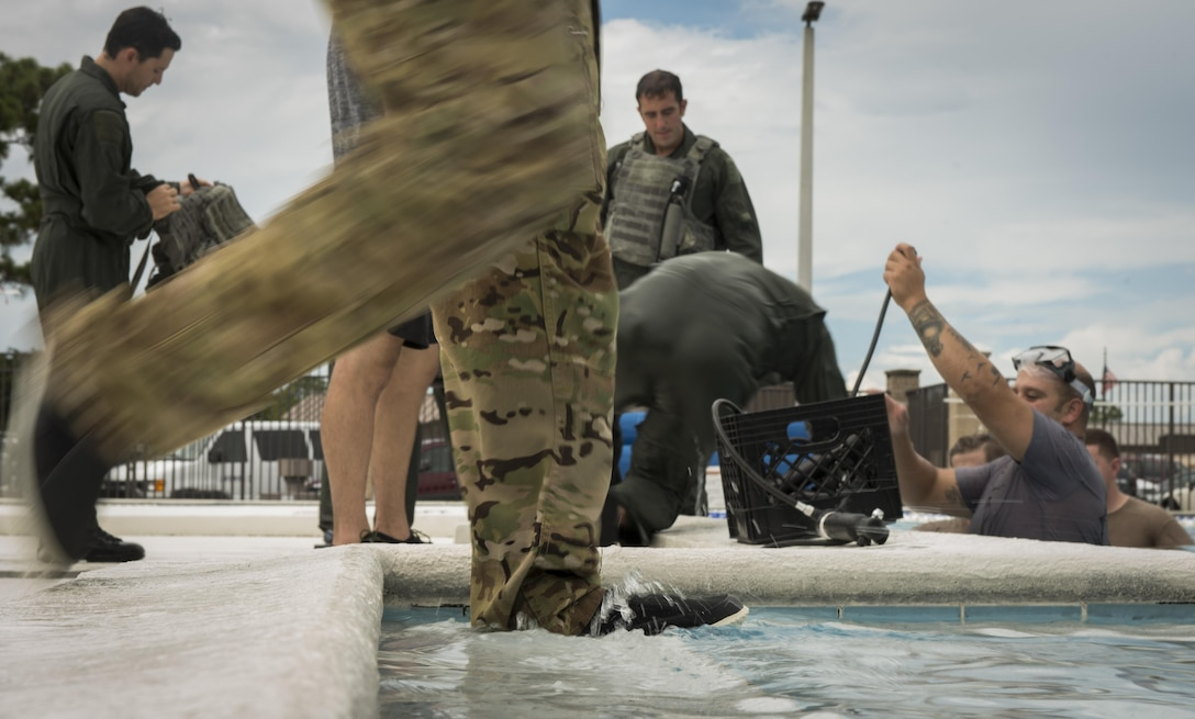 An 8th Special Operations Squadron aircrew member enters the base pool for rotary wing water survival training at Hurlburt Field, Fla., July 18, 2017. The 1st SOSS SERE specialists with the 1st Special Operations Support Squadron conduct rotary wing water survival training quarterly to ensure aircrew are proficient on emergency procedure skill sets. (U.S. Air Force photo by Airman 1st Class Joseph Pick)