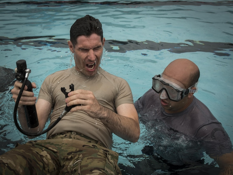 Staff Sgt. Anthony Fischer, right, a survival, evasion, resistance and escape specialist with the 1st Special Operations Support Squadron, supervises as a pilot with the 8th Special Operations Squadron surfaces after testing his oxygen tank under water during rotary wing water survival training at Hurlburt Field, Fla., July 18, 2017. More than 10 aircrew members performed emergency exit procedures while submerged under water in a simulated inverted helicopter crash. (U.S. Air Force photo by Airman 1st Class Joseph Pick)