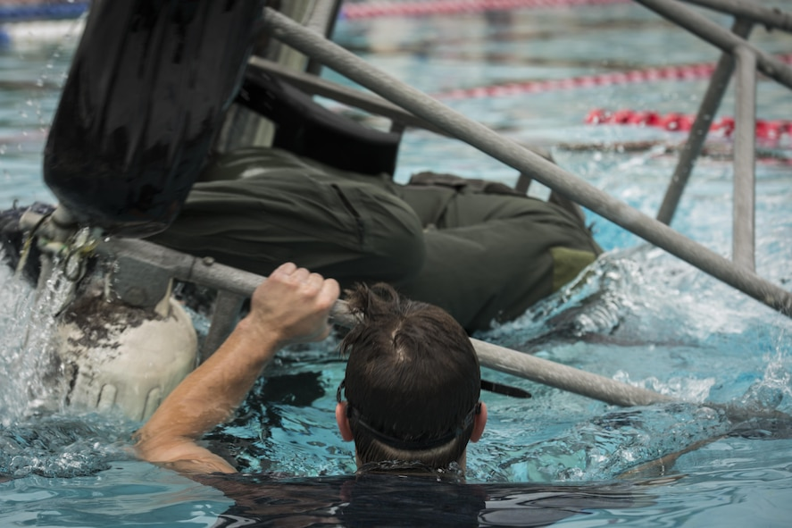 A survival, evasion, resistance and escape specialist with the 1st Special Operations Support Squadron flips a shallow water egress trainer chair during rotary wing water survival training at Hurlburt Field, Fla., July 18, 2017. The SWET chair allows aircrew members to practice escape procedures while submerged under water during a simulated inverted helicopter crash. (U.S. Air Force photo by Airman 1st Class Joseph Pick)