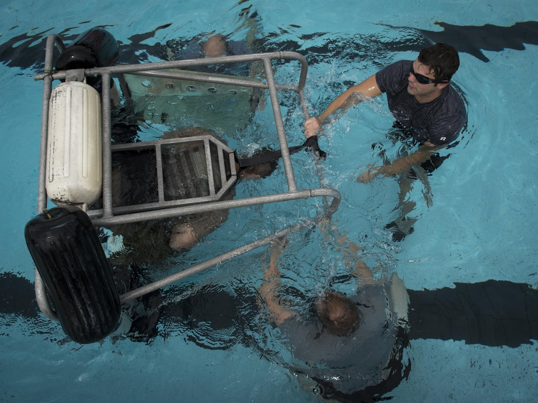 Survival, evasion, resistance and escape specialists with the 1st Special Operations Support Squadron submerge an 8th Special Operations Squadron aircrew member in a shallow water egress trainer chair during rotary wing water survival training at Hurlburt Field, Fla., July 18, 2017. The 1st SOSS SERE specialists conduct rotary wing water survival training quarterly to ensure aircrew are proficient on emergency procedure skill sets. (U.S. Air Force photo by Airman 1st Class Joseph Pick)