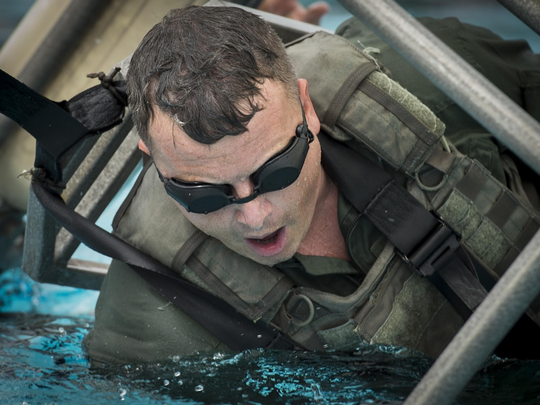Maj. Richard Fogel, a flight safety officer with Air Force Special Operations Command, prepares to be submerged during rotary wing water survival training at Hurlburt Field, Fla., July 18, 2017. Survival, evasion, resistance and escape specialists with the 1st Special Operations Support Squadron led rotary wing water survival training to ensure aircrew are proficient on emergency procedure skill sets if ever faced with a real-world incident. (U.S. Air Force photo by Airman 1st Class Joseph Pick)