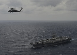 "BAY OF BENGAL (July 17, 2017) An MH-60S Sea Hawk Helicopter from the ""Eightballers"" of Helicopter Sea Combat Squadron (HSC) 8 hovers above the aircraft carrier USS Nimitz (CVN 68) during a photo exercise with the Indian Navy and Japan Maritime Self-Defense Force, July 17, 2017, in the Bay of Bengal as part of Exercise Malabar 2017. Malabar 2017 is the latest in a continuing series of exercises between the Indian Navy, JMSDF and U.S. Navy that has grown in scope and complexity over the years to address the variety of shared threats to maritime security in the Indo-Asia-Pacific region. (U.S. Navy photo by Mass Communication Specialist 3rd Class Cole Schroeder)"