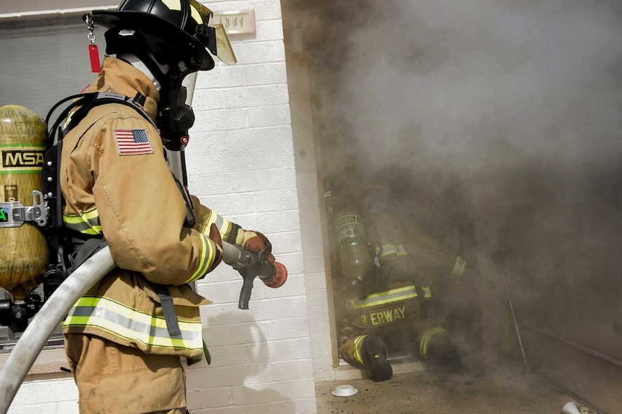 Staff Sgt. Blaine Erway, 99th Civil Engineer Squadron firefighter crew chief, and Airman 1st Class Brian Velten, 99th CES firefighter, prepare to enter a simulated house fire during Red Flag 17-3 at Nellis Air Force Base, Nev., July 18, 2017. The simulation tasked the pair with entering the house and recovering a dummy. (U.S. Air Force photo by Airman 1st Class Andrew D. Sarver/Released)