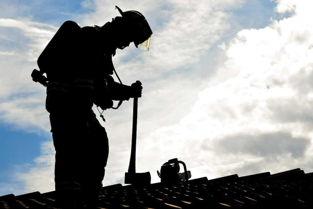 Airman 1st Class Adam Striejewski, 99th Civil Engineer Squadron firefighter, checks the roof of a simulated house fire during Red Flag 17-3 at Nellis Air Force Base, Nev., July 18, 2017. The increase of the base population during Red Flag exercises results in increased emergency calls to the fire department for anything from a minor medical emergency to a major flightline incident. (U.S. Air Force photo by Airman 1st Class Andrew D. Sarver/Released)