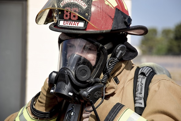 Staff Sgt. Blaine Erway, 99th Civil Engineer Squadron firefighter crew chief, adjusts his gas mask before entering a simulated house fire during Red Flag 17-3 at Nellis Air Force Base, Nev., July 18, 2017. Red Flag helps the firefighters train on and off the flightline to put their life-saving skills to the test. (U.S. Air Force photo by Airman 1st Class Andrew D. Sarver/Released)