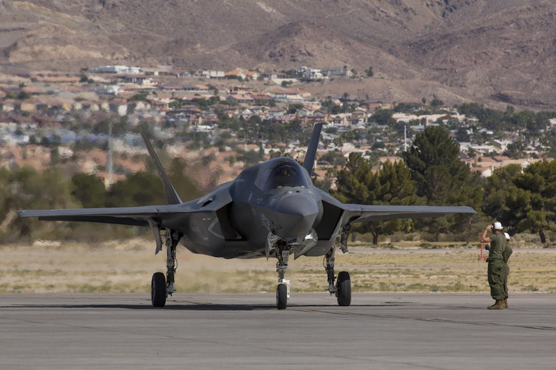 """Marines with Marine Fighter Attack Squadron (VMFA) 211 """"Wake Island Avengers,"""" 3rd Marine Aircraft Wing, salute each other after an F-35B Lightning II pilot landed at Nellis Air Force Base, Nev., July 5. A total of 10 aircraft and more than 250 Marines with VMFA-211 will participate in Red Flag 17-3, a realistic combat training exercise hosted by the U.S. Air Force to assess the squadron's ability to deploy and support contingency operations using the F-35B. Red Flag 17-3 begins July 10 and ends July 28. (U.S. Marine Corps photo by Sgt. Lillian Stephens/Released)"""