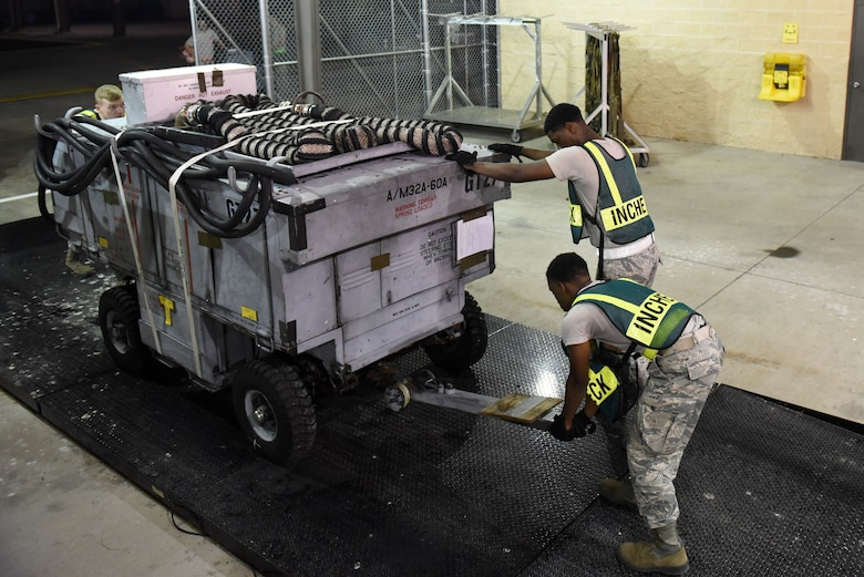 Members of the 4th Mission Support Group remove a generator cart from a weighing scale during exercise Thunderdome 17-02, July 20, 2017, at Seymour Johnson Air Force Base, North Carolina. The exercise allowed members of the 4th Fighter Wing to strengthen skills for real-world operations. (U.S. Air Force photo by Airman 1st Class Victoria Boyton)