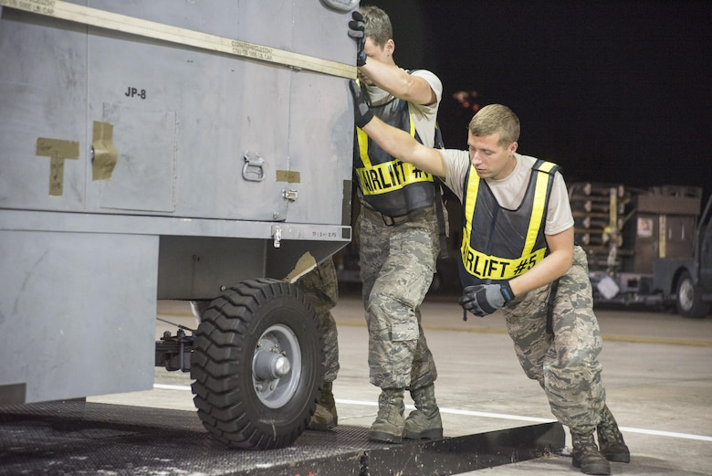Crew chiefs with the 4th Aircraft Maintenance Squadron push a hydrogen cart into a vehicle roll-on scale July 20, 2017, at Seymour Johnson Air Force Base, North Carolina. With the help of travel management office, the crew chiefs were able to weigh the cart prior to being loaded onto the aircraft. (U.S. Air Force photo by Tech. Sgt. David W. Carbajal)