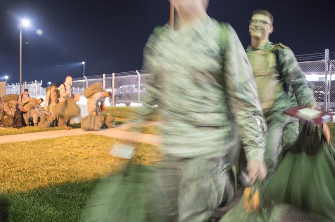 Airmen carry their deployment bags into the pre-deployment function processing center July 20, 2017, at Seymour Johnson Air Force Base, North Carolina. The processing line was a part of exercise Thunderdome 17-02, which is designed to evaluate the 4th Fighter Wing's ability to generate and deploy aircraft, Airmen and equipment. (U.S. Air Force photo by Tech. Sgt. David W. Carbajal)
