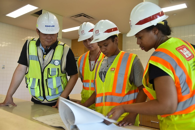 Joyrie Dickerson, center, a chemical engineering major from Hampton University, looks over a design package during a site visit July 20 at Camp Humphreys, South Korea.
