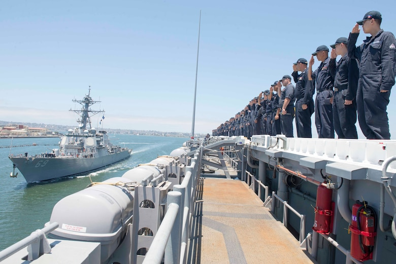 PACIFIC OCEAN (July 14, 2017) Sailors assigned to Wasp-class amphibious assault ship USS Essex (LHD 2) return salutes to the Arleigh Burke class guided-missle destroyer USS Milius (DDG 69).