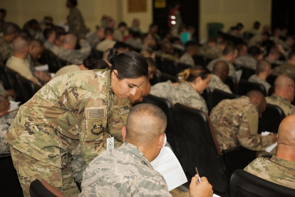 Staff Sgt. Beatriz Zapien, a personnelist assigned to the 386th Expeditionary Force Support Squadron Personnel Support for Contingency Operations sustainment team assists a newcomer with paperwork during an in-processing briefing at an undisclosed location in Southwest Asia, July 16, 2017. PERSCO conducts in-processing briefings with all inbound personnel to ensure 100% accountability as well as to provide a one stop shop for briefings and paperwork processing. (U.S. Air Force photo by Tech. Sgt. Jonathan Hehnly)