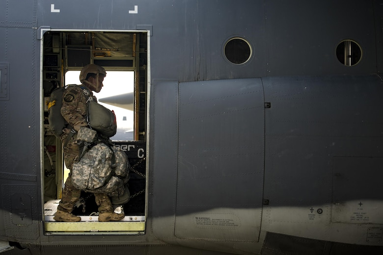An Airman from the 820th Base Defense Group walks past the crew door in an HC-130J Combat King II, July 14, 2017, at Moody Air Force Base, Ga. The 820th BDG includes airborne-qualified Airmen to support the expeditionary Air Force's only worldwide deployable, first-in, self-sustaining force protection capability. (U.S. Air Force photo/Staff Sgt. Ryan Callaghan)