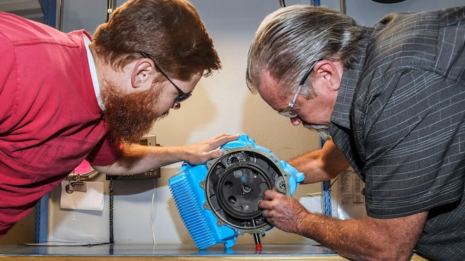 Mechanical Engineer Vance Bowman, left, and Equipment Specialist Rick Blickfeldt, both 419th Supply Chain Management Squadron, examine an A-10 aircraft Auxiliary Power Unit gear box at Hill Air Force Base, June 23. (U.S. Air Force)