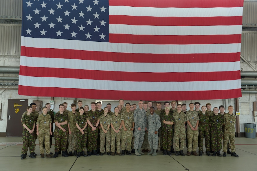 Royal Air Force Air Cadets and U.S. Air Force Airmen pose for a group photo at Hangar 1 on Spangdahlem Air Base, Germany, July 20, 2017. The cadets visited several different squadrons around base to give them a glimpse into U.S. Air Force operations. (U.S. Air Force photo by Staff Sgt. Jonathan Snyder)