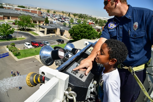 Captain Richard Partington, 775th Civil Engineering Squadron, shows Ilias Braxton how to operate a water cannon during a 'Military in Action event,' Hill Air Force Base, Utah, July 18, 2017. Event attendees were given demonstrations and access to equipment by units from across Hill AFB. (U.S. Air Force photo/R. Nial Bradshaw)